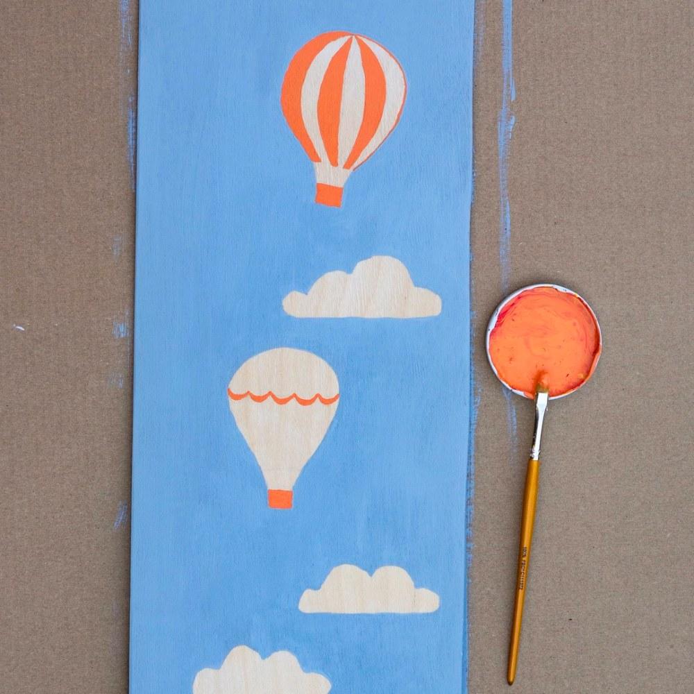Do dětského pokoje se hodí například motivy horkovzdušných balonů a mraků nebo můžete po celé jeho délce nakreslit žirafu či strom. Až barvy zaschnou, vyznačte na jedné straně metru tenkým štětcem či fixem číselné údaje. Metr doporučujeme zavěsit do výšky 60 cm nad zemí a čísla zapisovat vždy po pěticentimetrových úsecích.